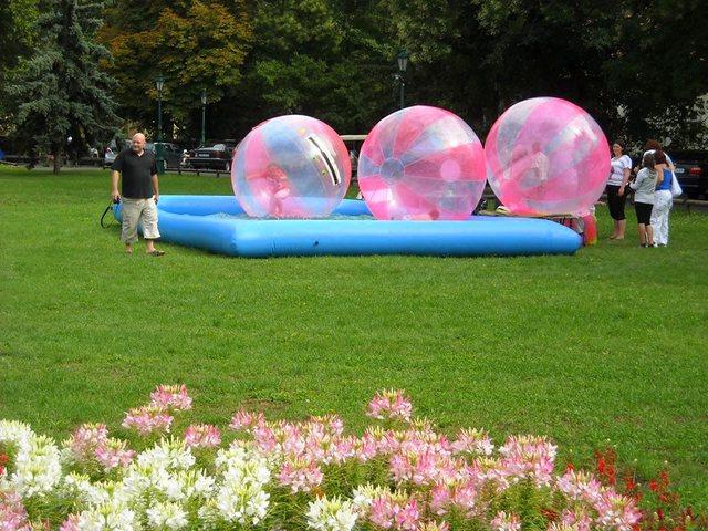 Intr-un bazin gonflabil umplut cu apa pluteau niste sfere gigant in care intra cate un copil