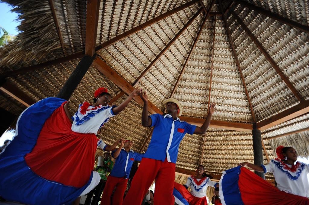 Barbati si femei din Republica Dominicana dansand in costume traditionale pe insula Catalina