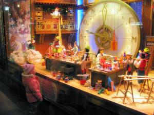 Copil in geamul unui magazin cu jucarii de Craciun