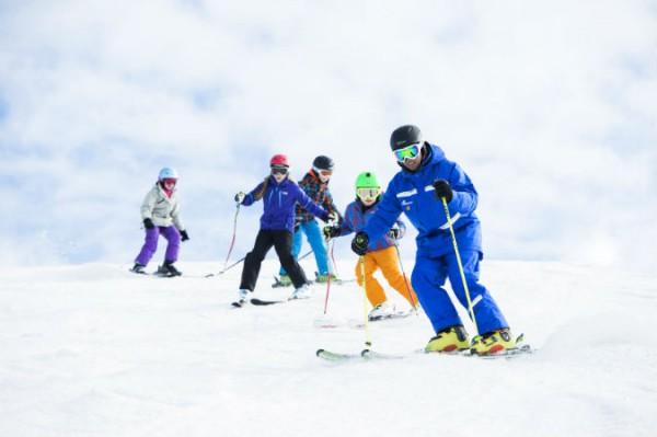 copii pe partia de ski impreuna cu instructorul